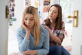 Teenage Girl Comforting Unhappy Friend In Bedroom Royalty Free Stock Photo