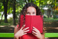 Teenage girl with curly hair reading book close up portrait of a hiding behind Royalty Free Stock Images