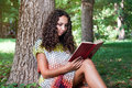 Teenage girl with curly hair reading book close up portrait of a in park Royalty Free Stock Photography