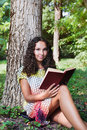 Teenage girl with curly hair reading book portrait of a in park Royalty Free Stock Photos