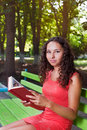 Teenage girl with curly hair reading book portrait of a in park Royalty Free Stock Photo