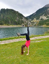 Teenage girl doing acrobatics in front of a lake the val de nuria reservoir the spanish pyrenees mountains Stock Images