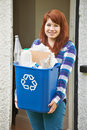 Teenage girl emptying recycling at home empties Stock Photo