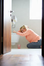 Teenage girl feeling unwell in bathroom at home sitting on floor by toilet sick Stock Images