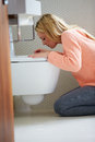 Teenage girl feeling unwell in bathroom sitting on floor by toilet Royalty Free Stock Images