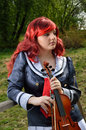Teenage girl with a fiddle is standing violin outdoors she is wearing an anime costume and wig Stock Photography