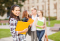 Teenage girl with folders and mates on the back summer holidays education campus concept smiling classmates Stock Image