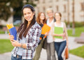 Teenage girl with folders and mates on the back summer holidays education campus concept smiling classmates Stock Photography