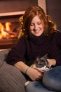 Teenage girl fondling cat at home Stock Images