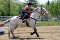 Teenage Girl Galloping Past A Barrel During A Barrel Race