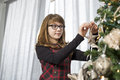 Teenage girl hanging ornament on christmas tree at home Royalty Free Stock Images