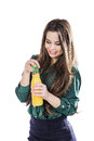 Teenage girl happy while holding a bottle of orange juice.in a green blouse. isolated on a white background.opens a bottle