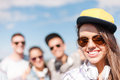 Teenage girl with headphones and friends outside summer holidays concept in sunglasses cap hanging out Royalty Free Stock Image