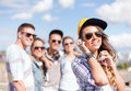Teenage girl with headphones and friends outside summer holidays concept in sunglasses cap hanging out Stock Photos
