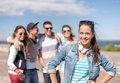Teenage girl with headphones and friends outside summer holidays concept in sunglasses hanging out Royalty Free Stock Images