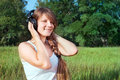 Teenage girl with headphones listening to music in the park portrait of a Royalty Free Stock Image
