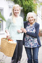Teenage girl helping senior woman to carry shopping portrait of Royalty Free Stock Photography