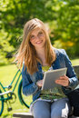 Teenage girl holding digital tablet in park sitting with the sunny Stock Images