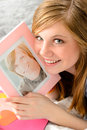 Teenage girl holding picture of her love smiling a Stock Photography