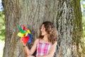 Teenage girl holding pinwheel portrait of happy while leaning on tree trunk Stock Image