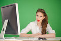 Teenage girl incredulous attractive sitting in front of computer on desk top looking puzzled or green background Stock Photos