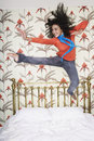 Teenage Girl Jumping On Bed
