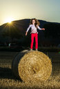 Teenage girl jumping from the haystack