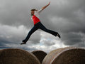 Teenage girl jumping over hay bales.