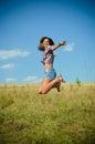 Teenage girl jumping on summer field