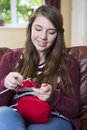 Teenage girl knitting at home enjoying traditional craft hobby Royalty Free Stock Photos