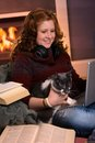 Teenage girl learning at home with cat smiling sitting fireplace laptop and books happy brainy preoccupation Royalty Free Stock Photo