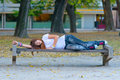 Teenage girl lies on the bench in the park Stock Image