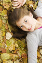 Teenage girl lying down with leaves around. Royalty Free Stock Image