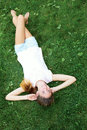 Teenage girl lying on the grass. woman relaxation outdo Royalty Free Stock Photo