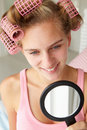 Teenage girl with mirror and hair curlers Royalty Free Stock Photography