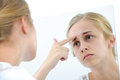 Teenage girl with mirror teenager checking her face for pimple in the Royalty Free Stock Image