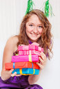Teenage girl in a party dress cute cheerful with pile of gift boxes Royalty Free Stock Image