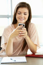 Teenage girl with phone in class Royalty Free Stock Photo