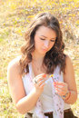 Teenage girl picking flower petals, shiny springtime scenery out Royalty Free Stock Photo
