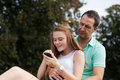 Teenage girl playing on her phone while father is watching it over shoulder Royalty Free Stock Photography