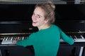 Teenage girl plays piano in green shirt Royalty Free Stock Photo