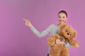 Teenage girl pointing happy teenage girl holding a teddy bear a and away while isolated on coloured background Stock Image