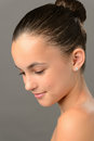 Teenage girl purity skin beauty looking down face on gray Stock Photos