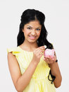 Teenage girl putting money into piggy bank smiling to camera Royalty Free Stock Image