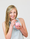 Teenage girl putting money into piggy bank smiling to camera Royalty Free Stock Photography