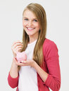 Teenage girl putting money into piggy bank smiling to camera Stock Photos