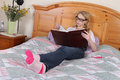 Teenage girl reading in bed Royalty Free Stock Photo
