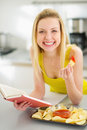 Teenage girl reading book and eating chips in modern kitchen Stock Photos