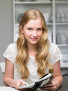 Teenage girl reading magazine smiling to camera Royalty Free Stock Photos