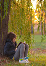 Teenage girl reads the book under the willow tree Royalty Free Stock Photo